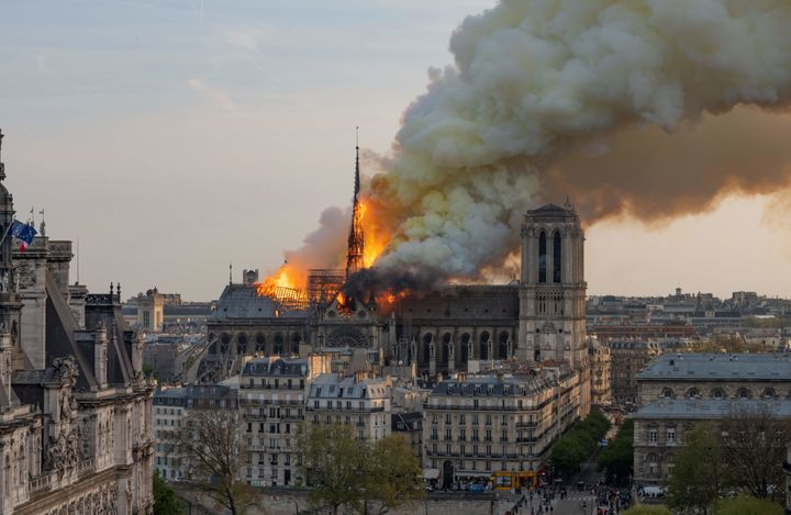 Smoke billows as flames burn through the roof of Notre Dame on Monday. (Photo by Fabien Barrau / AFP)