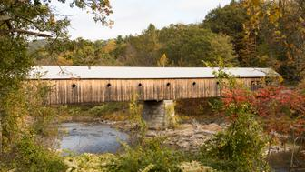 Fall foliage on tree lined banks of river with oldest covered wooden bridge in Vermont.