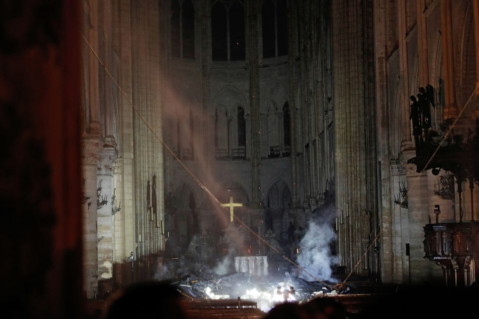 Smoke rises around the altar in front of the cross inside the Notre Dame