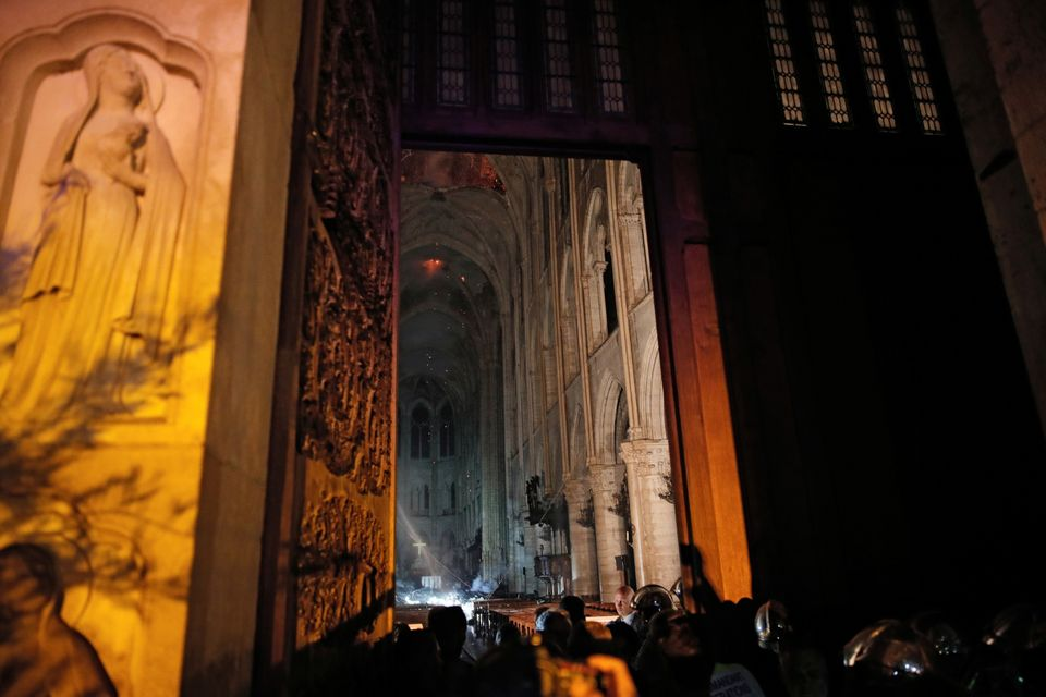 General view from the entrance shows smoke rising around the altar in front of the cross inside the Notre...