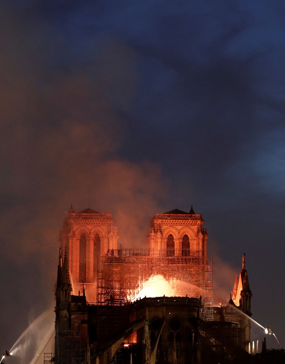 Flames engulf the roof at Notre Dame cathedral as firefighters battle to extinguish the fire on Monday