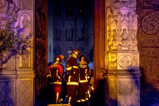 Un grupo de bomberos, evaluando daños a las puertas de Notre