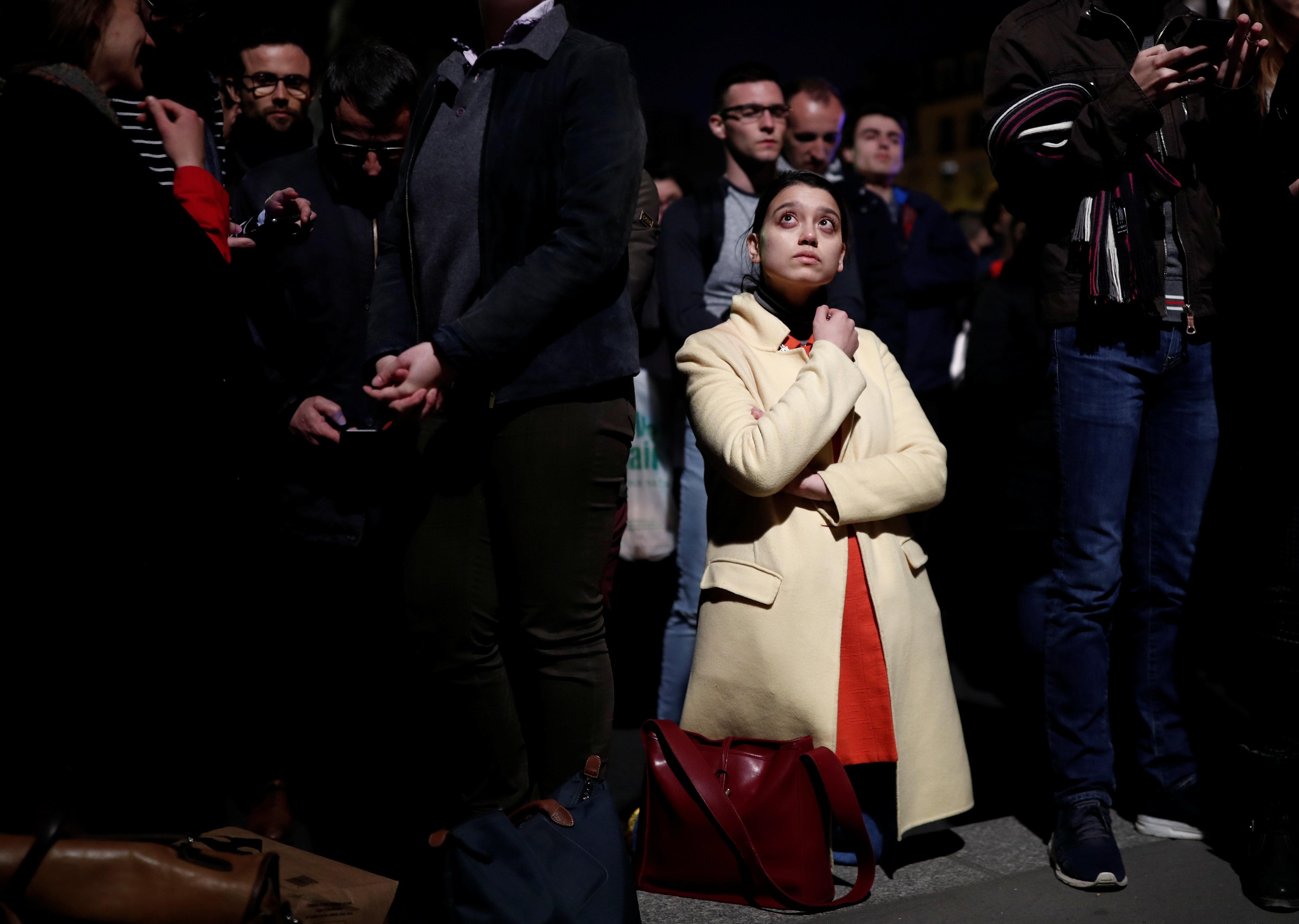 Varias personas contemplan sobrecogidas el incendio de Notre Dame