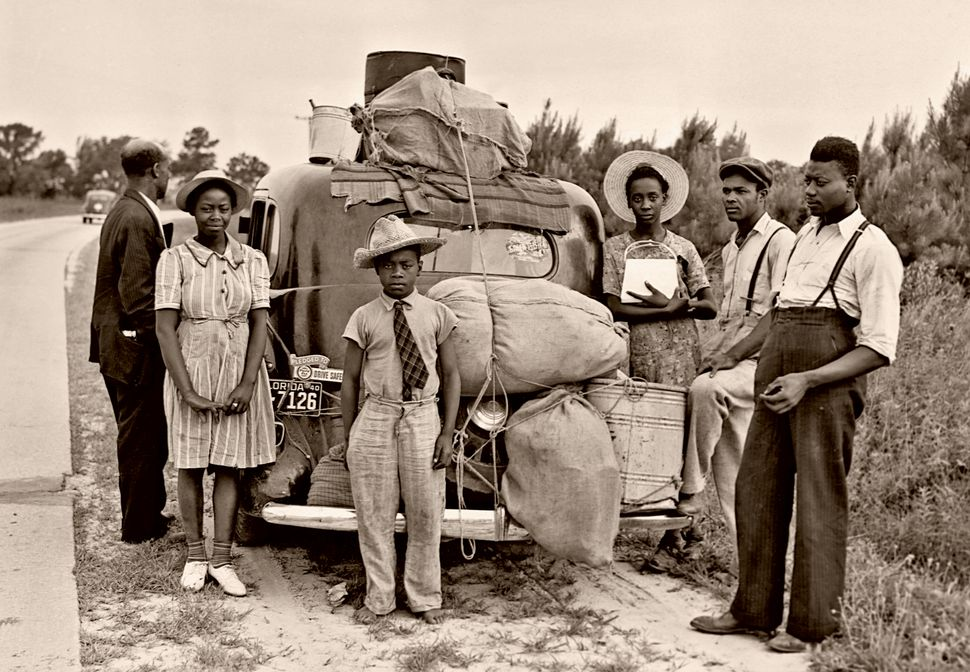 Migrant workers from Florida take a roadside break in Shawboro, North Carolina, on their way to pick...