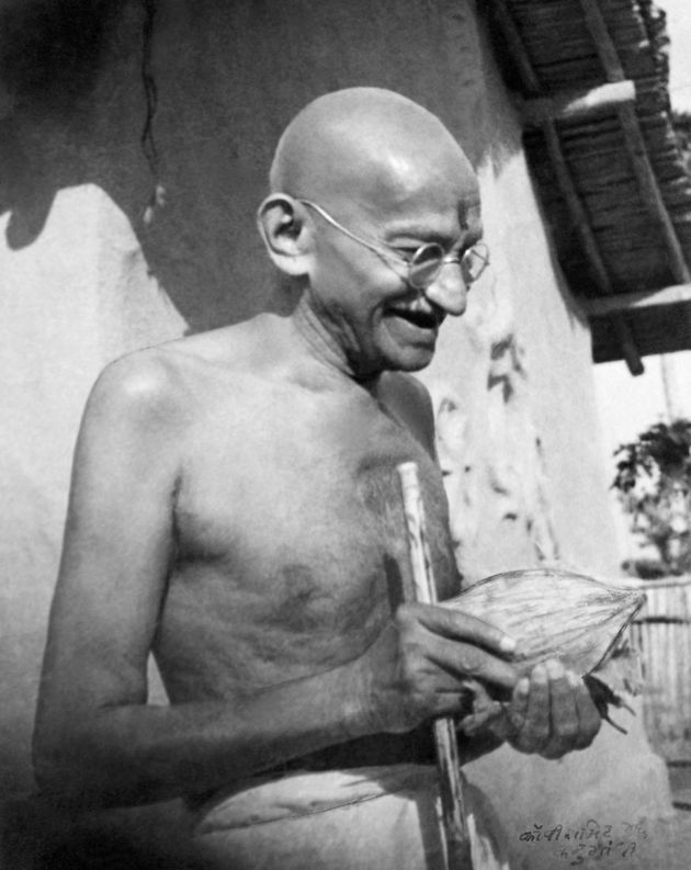 Gandhi, who was known to love fruit, receives a coconut in front of his hut at Sevagram Ashram in January