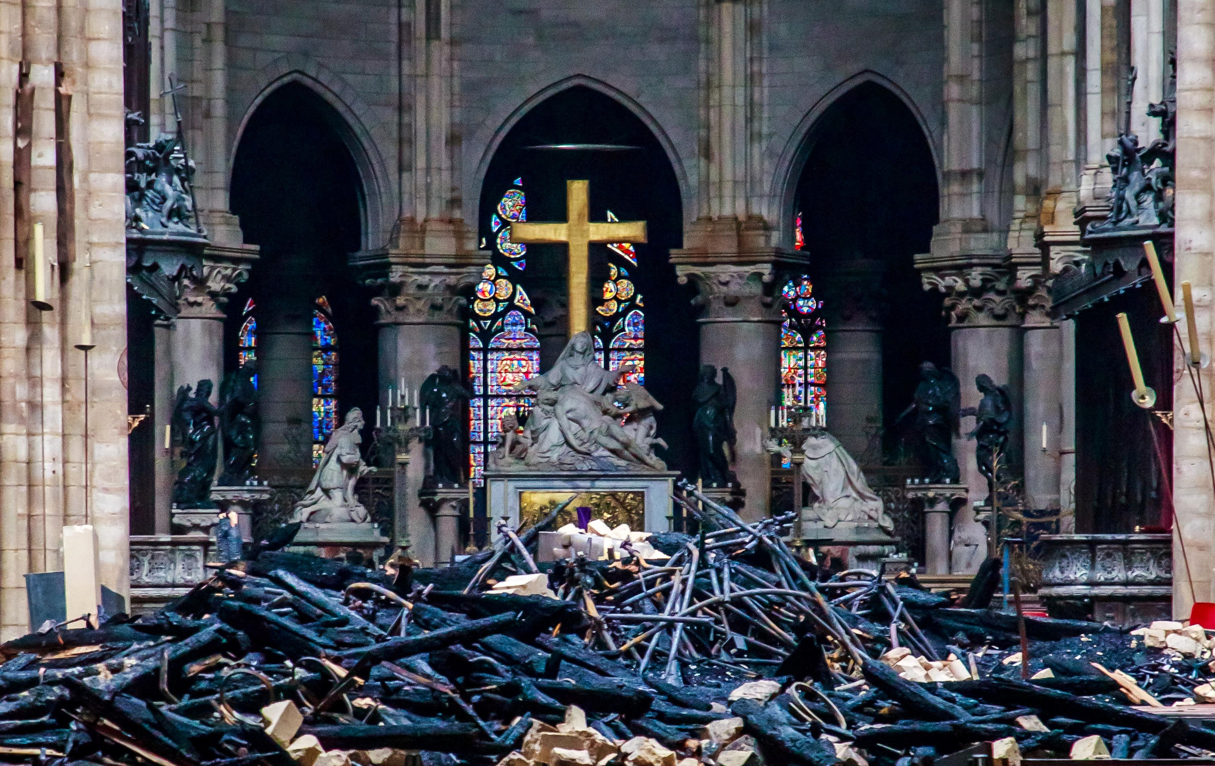 A view of the cross and sculpture of Pieta by Nicolas Coustou in the background of debris inside Notre-Dame de Paris, in the aftermath of a fire that devastated the cathedral, during the visit of French Interior Minister Christophe Castaner (not pictured) in Paris, France, April 16, 2019. Christophe Petit Tesson/Pool via REUTERS