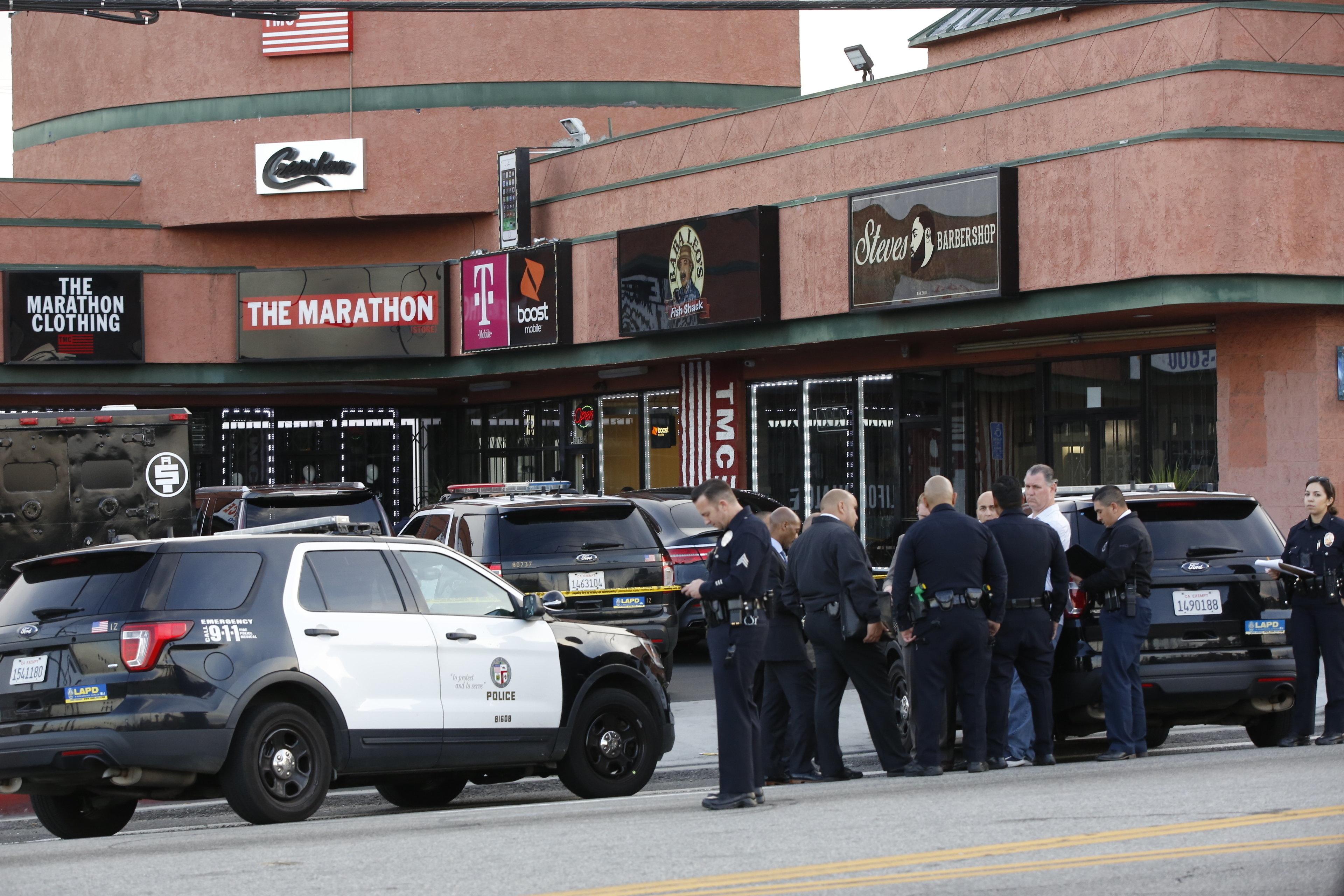 Policías se congregan alrededor de la tienda Marathon Clothing del rapero Nipsey Hussle en Los Angeles, el domingo 31 de marzo del 2019. Hussle, un respetado rapero nominado este año al Grammy, fue asesinado a tiros el domingo. Tenía 33 años. (AP Foto/Damian Dovarganes)