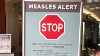 FILE - In this Jan. 30, 2019 file photo signs posted at The Vancouver Clinic in Vancouver, Wash., warn patients and visitors of a measles outbreak. A measles outbreak near Portland, Ore., has revived a bitter debate over so-called personal belief exemptions to childhood vaccinations. Four percent of Washington secondary school students have non-medical vaccine exemptions. (AP Photo/Gillian Flaccus,File)