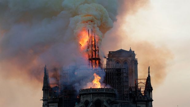 TOPSHOT - The steeple and spire engulfed in flames collapses as the roof of the Notre-Dame de Paris Cathedral burns on April 15, 2019 in Paris. - A colossal fire swept through the famed Notre-Dame Cathedral in central Paris on April 15, 2019, causing a spire to collapse and raising fears over the future of the nearly millenium old building and its precious artworks. The fire, which began in the early evening, sent flames and huge clouds of grey smoke billowing into the Paris sky as stunned Parisians and tourists watched on in sheer horror. (Photo by Geoffroy VAN DER HASSELT / AFP)        (Photo credit should read GEOFFROY VAN DER HASSELT/AFP/Getty Images)