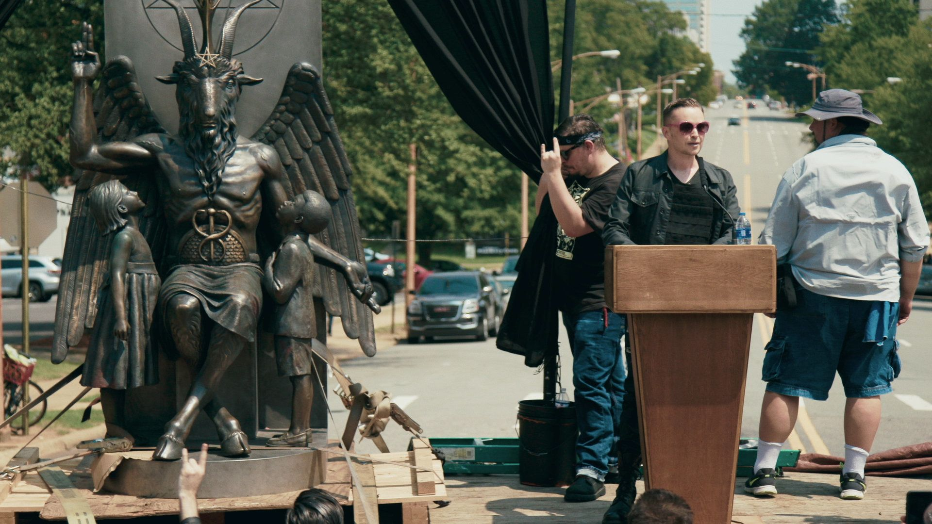 Satanic Temple co-founder Lucien Greaves delivers a speech in front of the Arkansas Capitol, with the group's Baphomet statue by his side.
