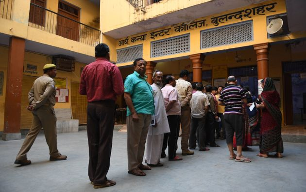 Voters queue up to cast their vote at a polling station in Bulandshahr, Uttar Pradesh on 18 April 2019,...
