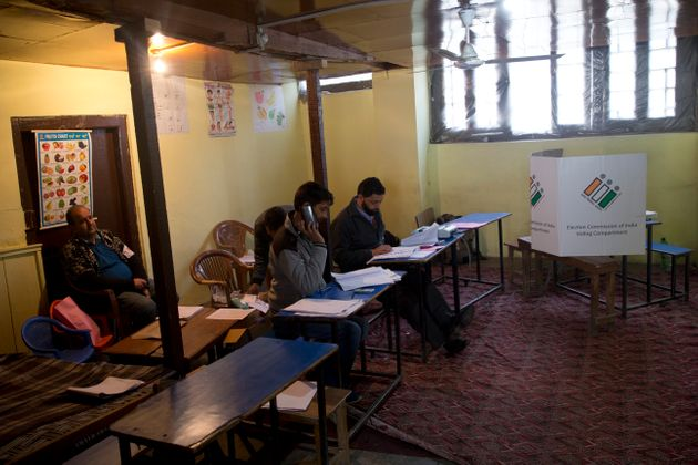 Election officers sit inside an empty polling station during the second phase of elections in