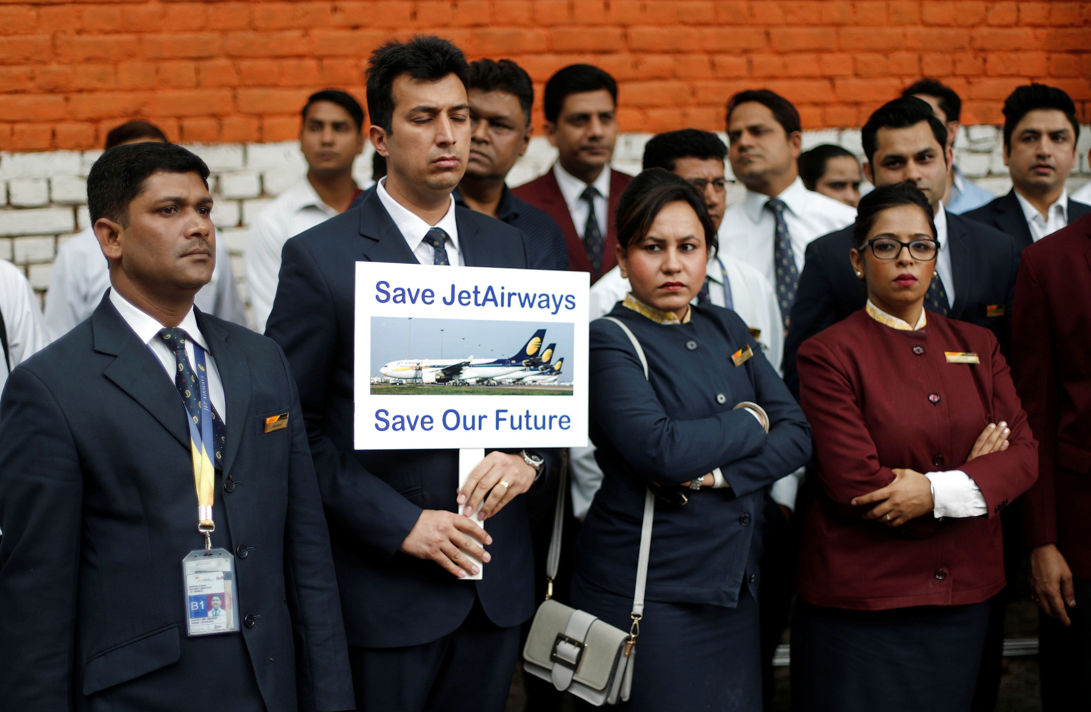 A Jet Airways employee holds a placard as he and others attend a protest demanding to