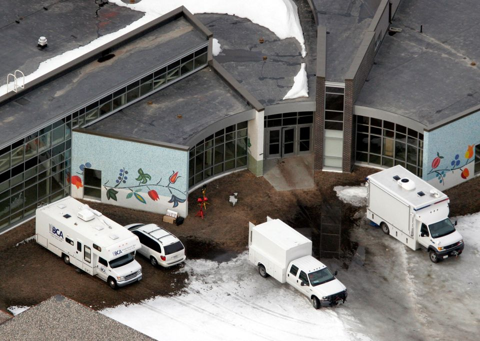 Police forensic vans sit outside of Red Lake Senior High School the day after the