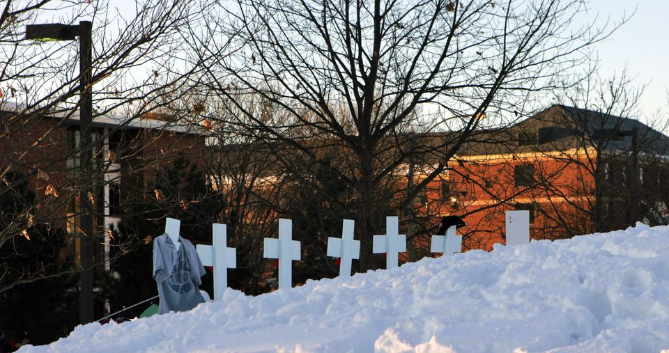 Crosses bearing the names of shooting victims placed on a hill overlooking the campus of Northern Illinois...