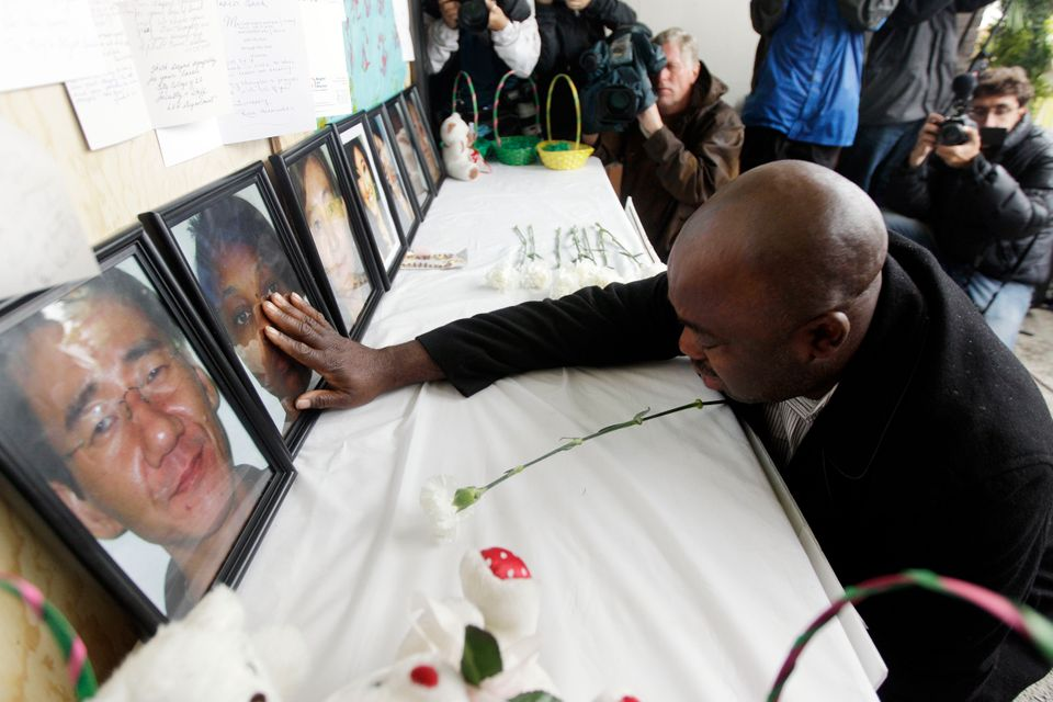 Efanye Chibuko touches a picture of his wife Doris during a memorial service at Oikos University the...