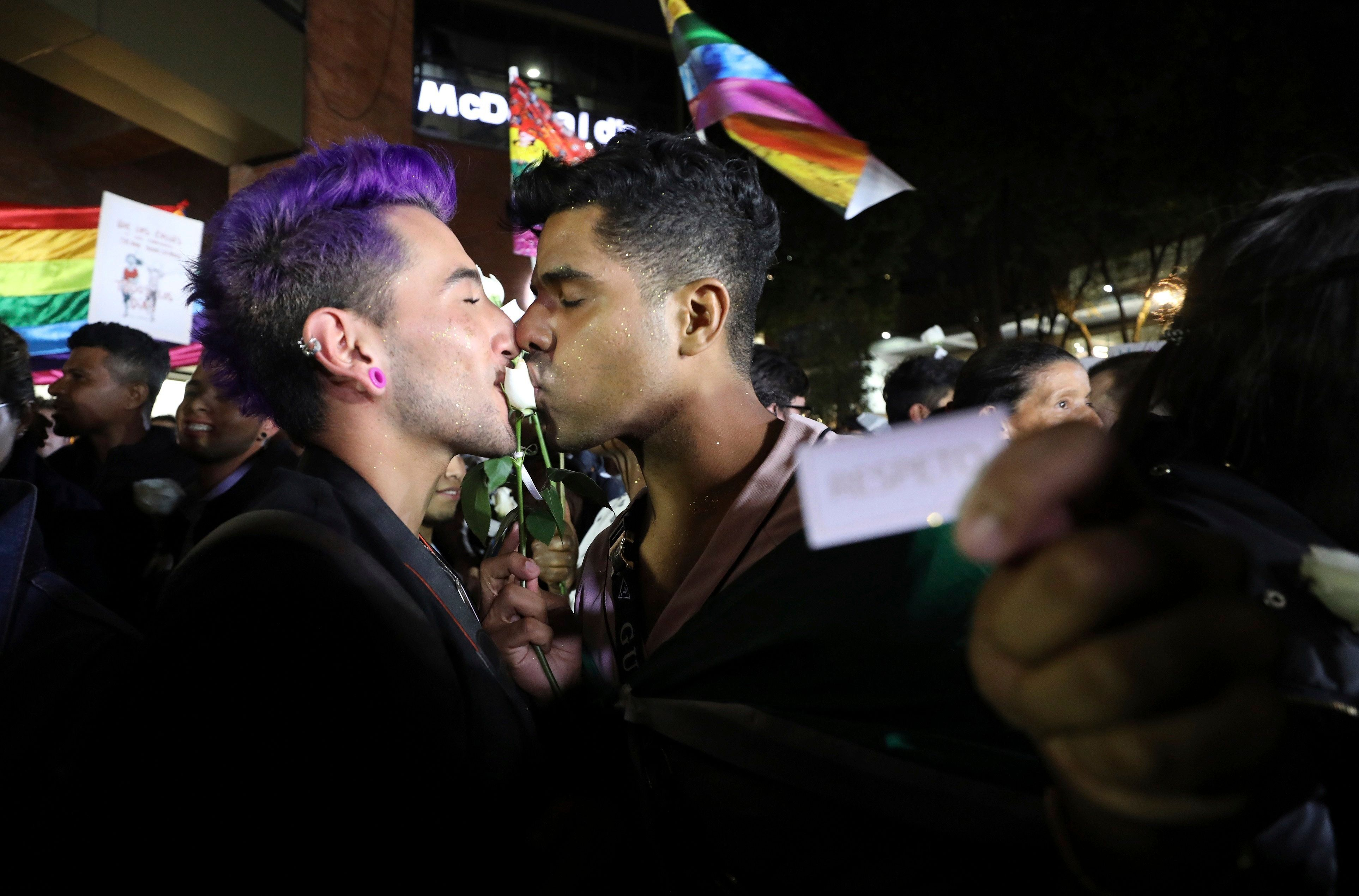 """A same sex couple kiss a rose during a """"Kiss-a-thon,"""" as a form of protest for LGBT rights in Bogota, Colombia, Wednesday, April 17, 2019. The event was held at the same Andino shopping mall where days ago two gay men were harassed by a customer who lured police into fining them for """"exhibitionism."""" (AP Photo/Fernando Vergara)"""