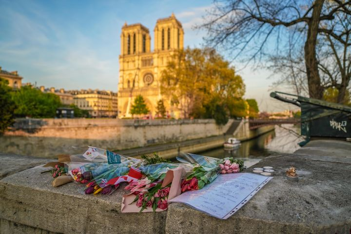 Flowers are placed in front of Notre Dame Cathedral on April 18, 2019 in Paris, France.