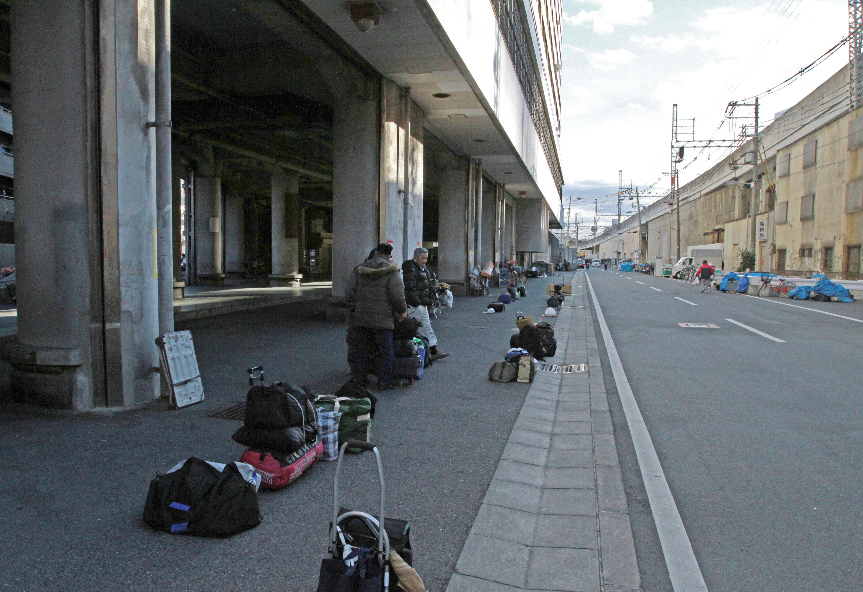 あいりん労働福祉センター前に荷物を置き、日雇い労働のあっせんを待つ人たち