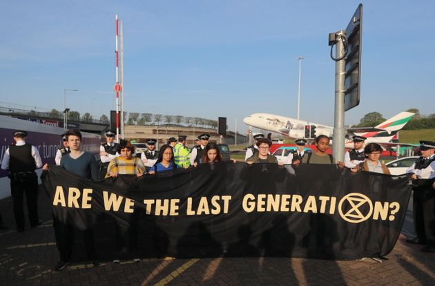 Young activists hold a banner at a protest near Heathrow Airport's main entrance on