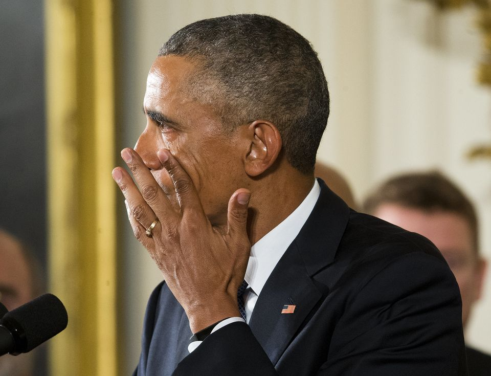 President Barack Obama wipes a tear running down his cheek as he talks about victims of the Sandy Hook...