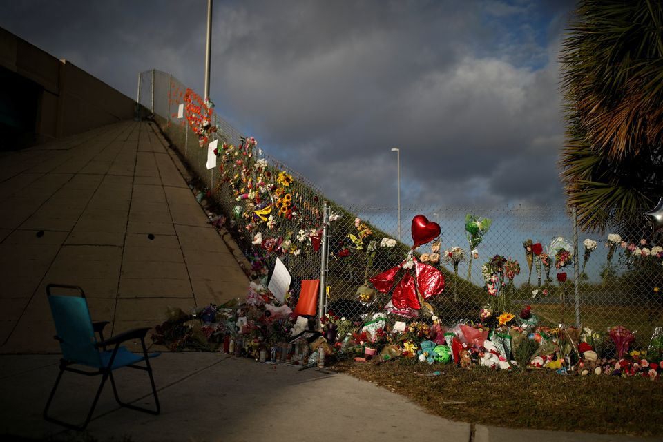 An empty chair is seen in front of flowers and mementoes placed on a fence to commemorate the victims...