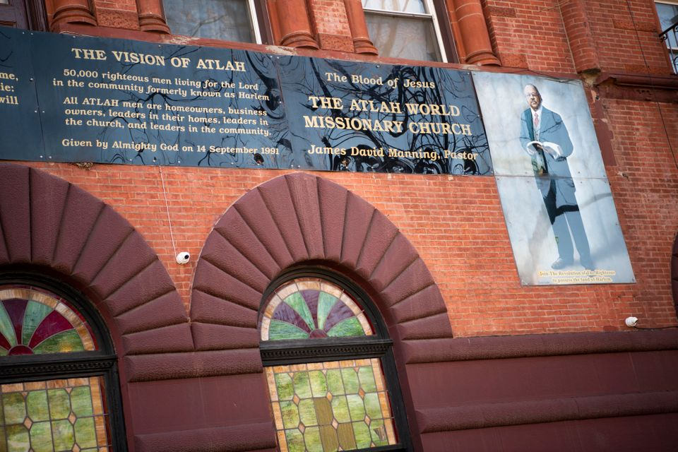 The exterior of Atlah World Missionary Church features a large portrait of