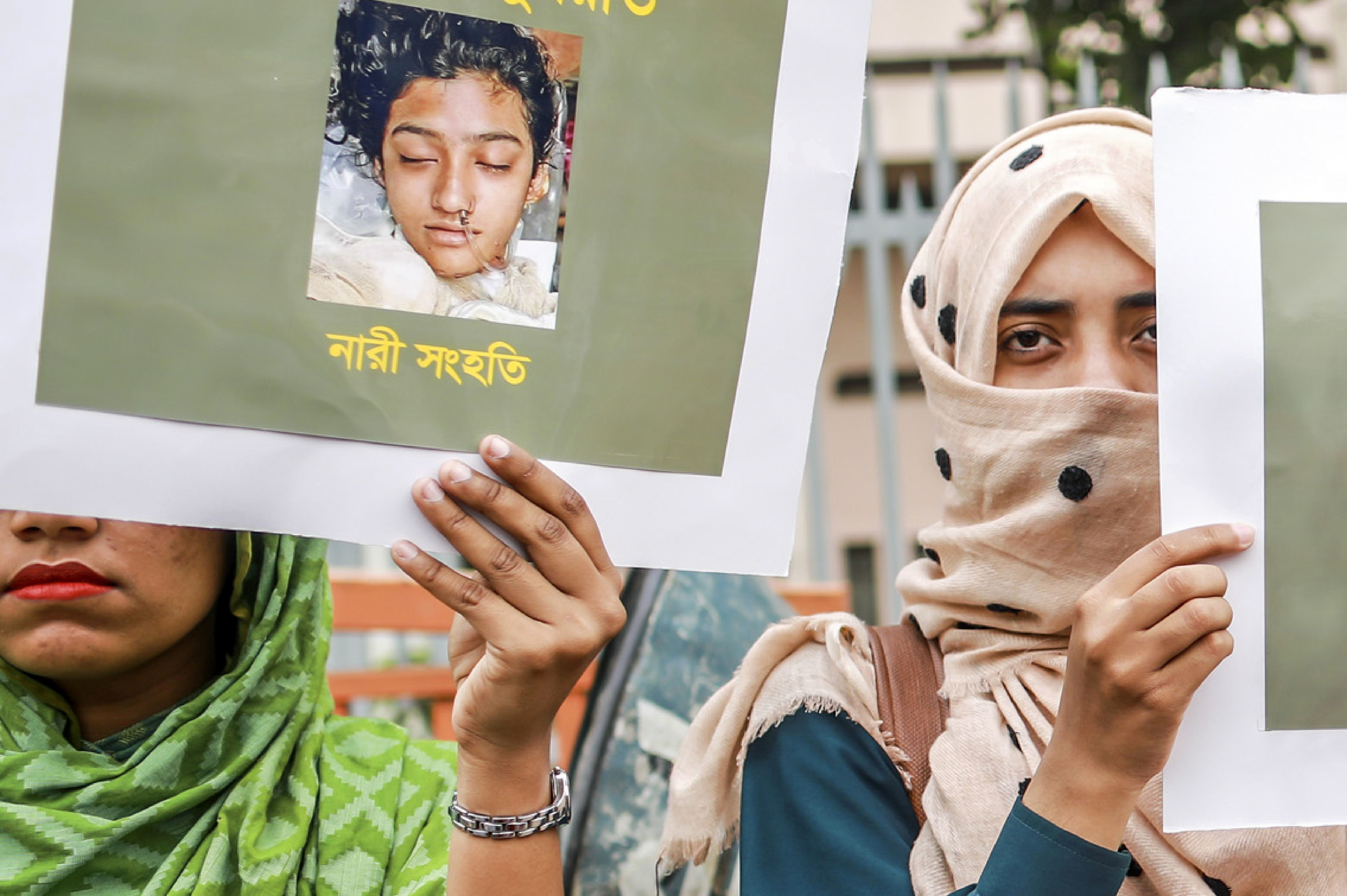 In this photo taken on April 12, 2019 Bangladeshi women hold placards and photographs of schoolgirl Nusrat Jahan Rafi at a protest in Dhaka, following her murder by being set on fire after she had reported a sexual assault. - A schoolgirl was burned to death in Bangladesh on the orders of her head teacher after she reported him for sexually harassing her, police said April 19. The death of 19-year-old Nusrat Jahan Rafi last week sparked protests across the South Asian nation, with the prime minister promising to prosecute all those involved. (Photo by SAZZAD HOSSAIN / AFP)        (Photo credit should read SAZZAD HOSSAIN/AFP/Getty Images)