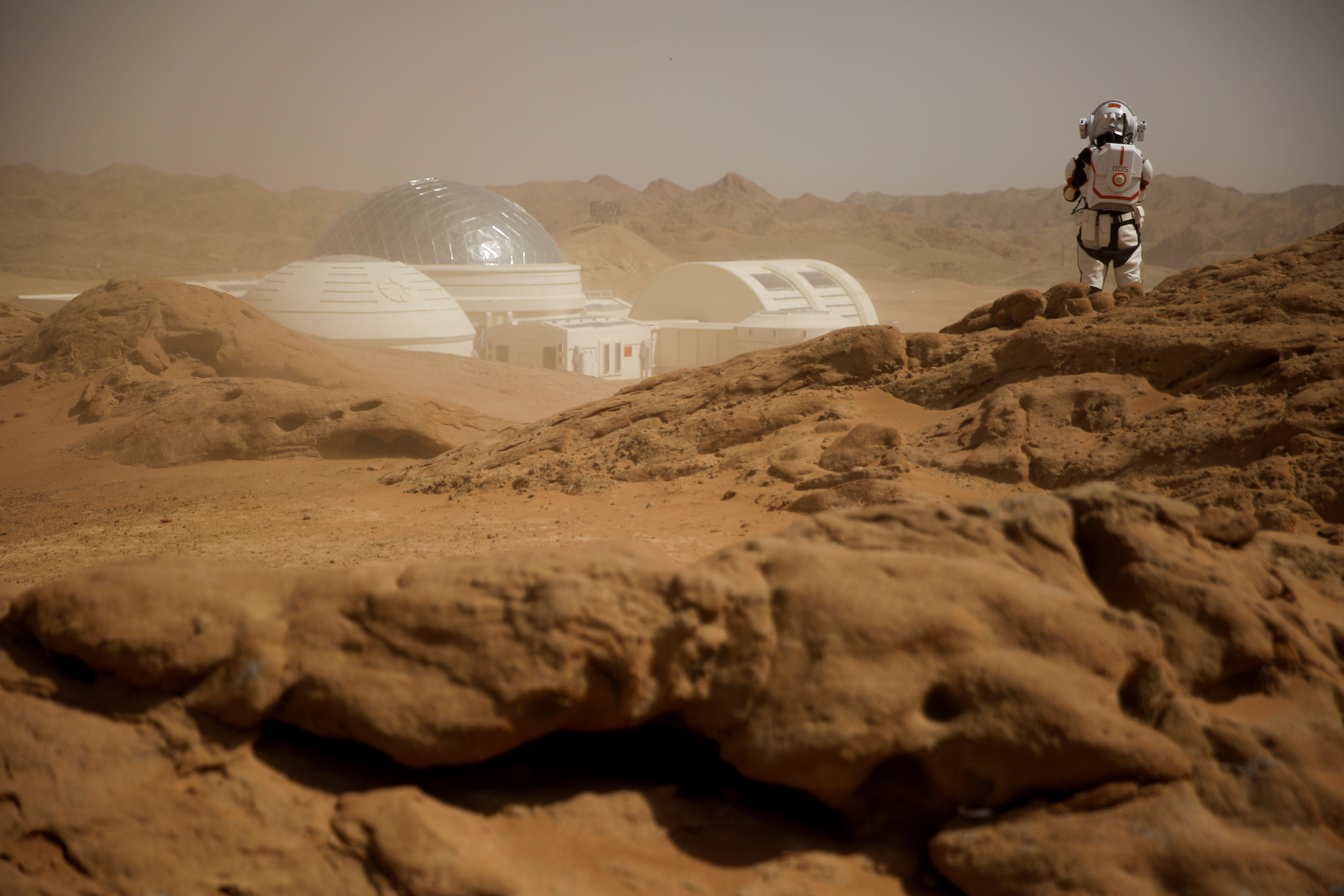 Sand whipped up by wind shrouds the C-Space Project Mars simulation base as a staff member wearing a mock space suit poses in the Gobi Desert outside Jinchang, Gansu Province, China, April 18, 2019.  REUTERS/Thomas Peter     TPX IMAGES OF THE DAY