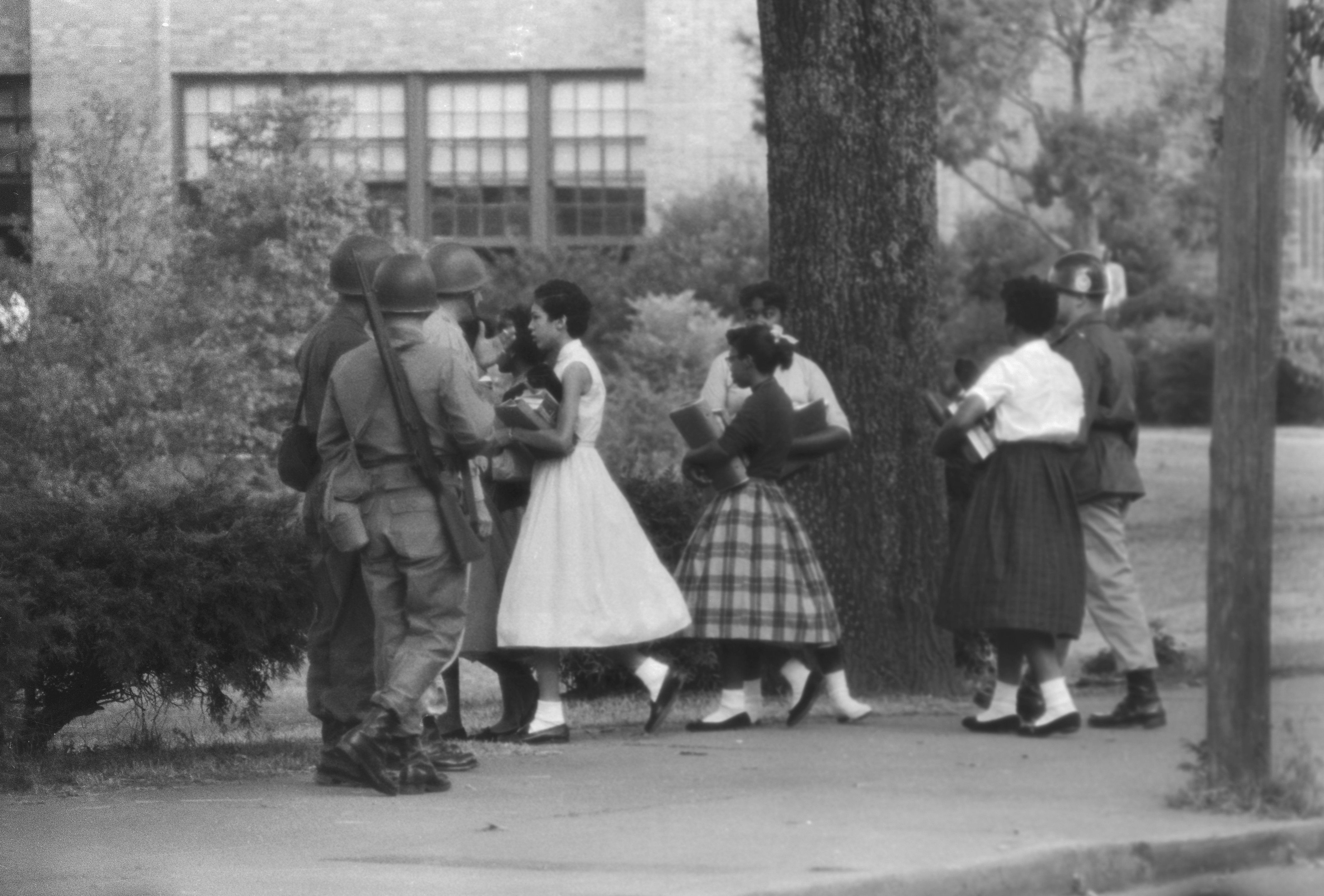 The group of nine African American students walk past members of the National Guard as they use a side door to enter Central High School in Little Rock, Arkansas, after the Federal court ordered the enforcement of desegregation laws. The students' previous attempts to enter the school were met by jeers from a crowd of onlookers and a group of white students blocking the main entrance.