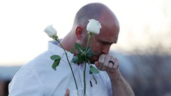 Will Beck, who was a sophomore at Columbine High School during the massacre nearly 20 years ago, reacts as he attends a vigil at the memorial for the victims of the attack Friday, April 19, 2019, in Littleton, Colo. (AP Photo/David Zalubowski)