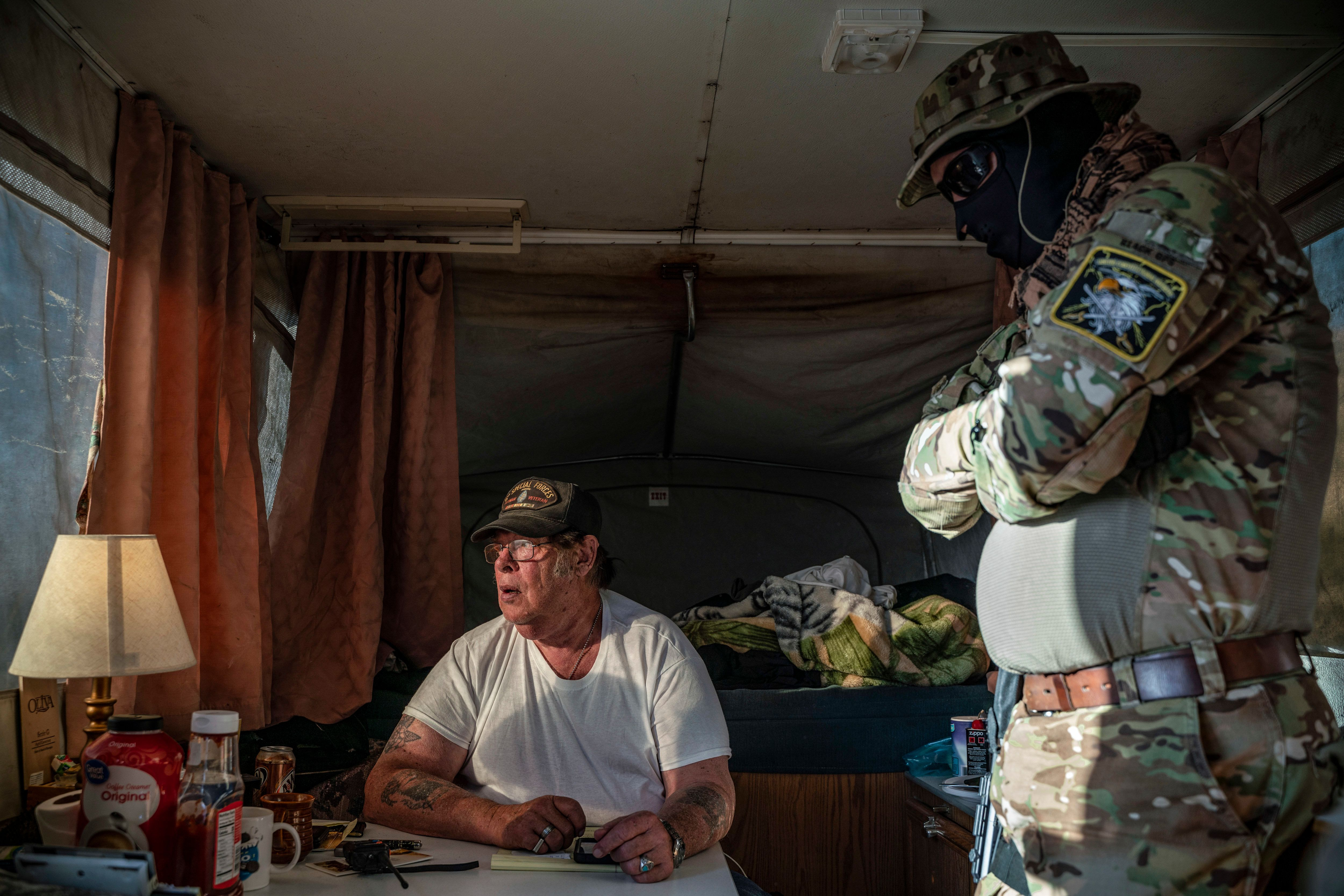 Striker, the leader of the Constitutional Patriots New Mexico Border Ops Team militia, speaks with Viper (R),  who go by aliases to protect their identity, inside the team's camper while discussing logistics on a group chat near the US-Mexico border in Anapra, New Mexico on March 20, 2019. - The militia members say they will patrol the US-Mexico border near Mt. Christo Rey, 'Until the wall is built.' In recent months, thousands of Central Americans have arrived in Mexico in several caravans in the hope of finding a better life in the United States. US President Donald Trump has branded such migrants a threat to national security, demanding billions of dollars from Congress to build a wall on the southern US border. (Photo by Paul Ratje / AFP)        (Photo credit should read PAUL RATJE/AFP/Getty Images)