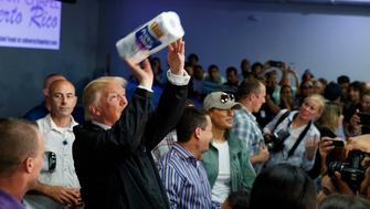 FILE - In this Oct. 3, 2017 file photo, President Donald Trump tosses paper towels into a crowd at Calvary Chapel in Guaynabo, Puerto Rico after Hurricane Maria devastated the region. Ever since President George W. Bush's administration was crippled by its response to Hurricane Katrina, politicians and news organizations have been acutely aware of the stakes raised by big storms.  (AP Photo/Evan Vucci, File)