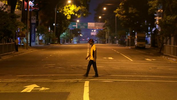 A Sri Lankan man walks across a deserted street during a curfew in Colombo, Sri Lanka, Sunday, April 21, 2019. More than two hundred people were killed and hundreds more injured in eight blasts that rocked churches and hotels in and just outside Sri Lanka's capital on Easter Sunday. (AP Photo/Eranga Jayawardena)