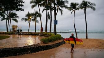 A surfer walks along Waikiki Beach in a light rain from Tropical Storm Lane, Saturday, Aug. 25, 2018, in Honolulu. (AP Photo/John Locher)