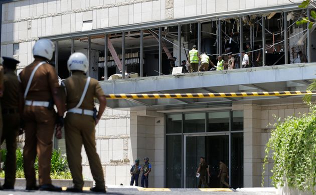 Police and forensic officials inspect a blast spot at the Shangri-la hotel in Colombo, Sri Lanka, Sunday,...