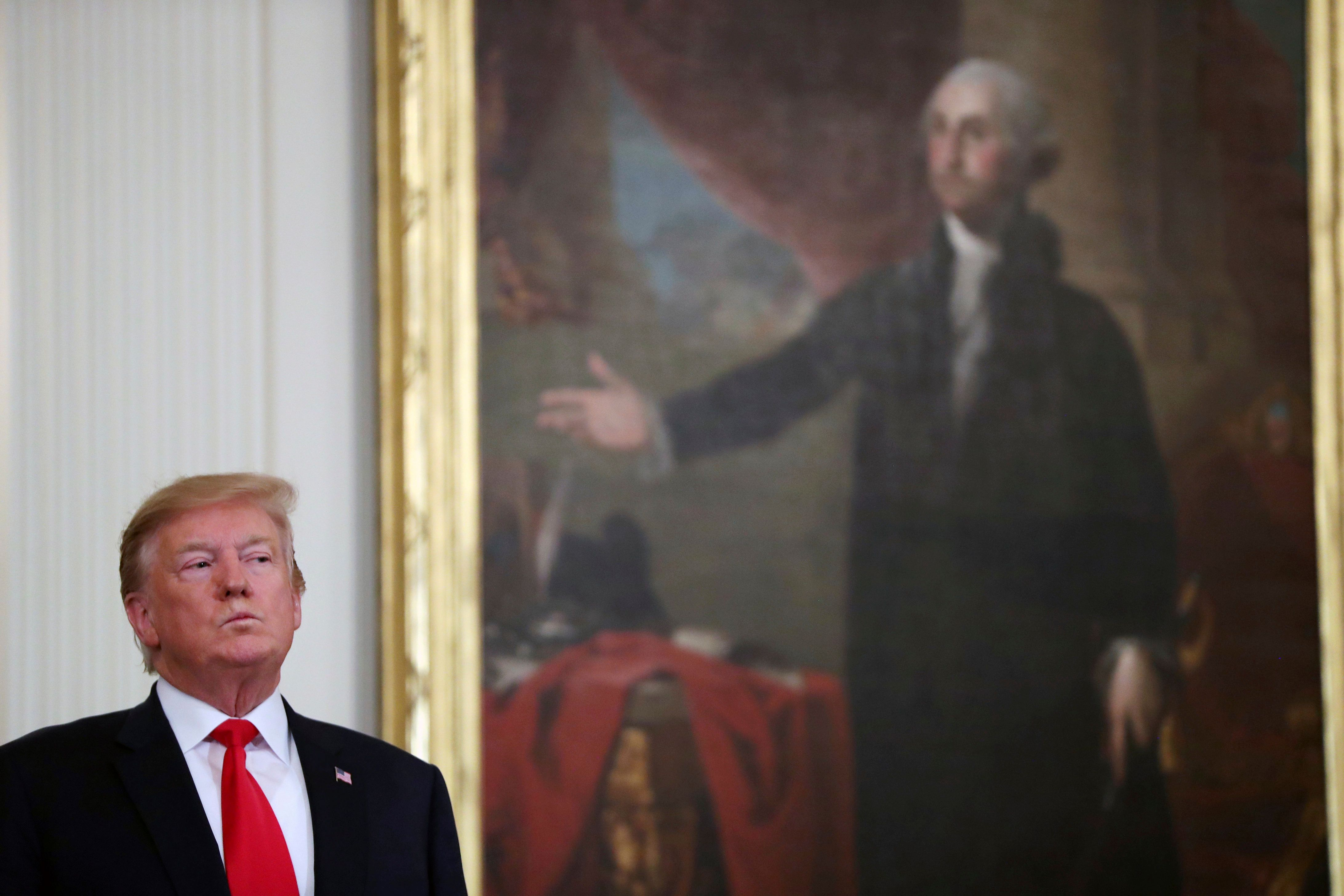 President Donald Trump stands near a portrait of George Washington at a Wounded Warrior Project Soldier Ride event in the East Room of the White House, Thursday, April 18, 2019, in Washington. (AP Photo/Andrew Harnik)