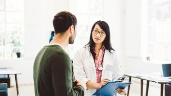 Confident female doctor talking to male patient while holding clipboard. Medical professional is looking at man in clinic. They are in hospital.