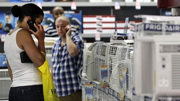 A shopper looks at air conditioners at a store in New York. More states are looking to phase out hydrofluorocarbons, or HFCs,