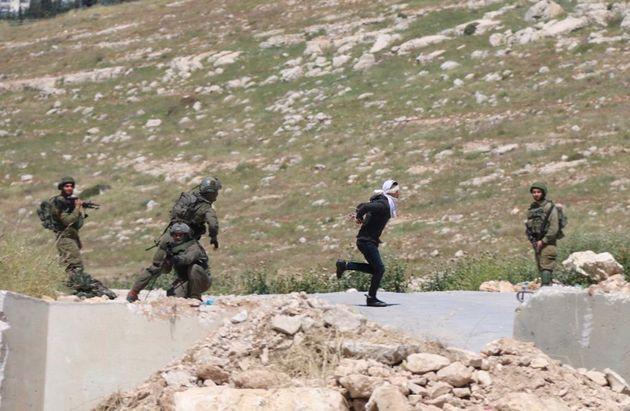El menor palestino, Osama Hajahjeh, corre con las manos atadas y los ojos vendados, mientras le persiguen...