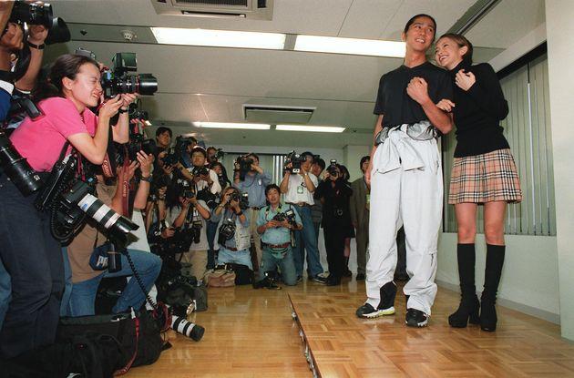 結婚報告会見の後、笑顔で指輪(カルティエの「ラブリング」)を披露する安室奈美恵さん。