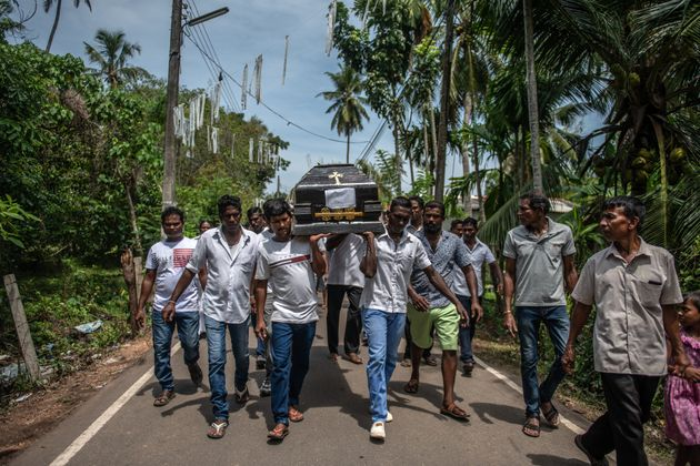 A coffin is carried to a burial site during a mass funeral at St Sebastian Church in Negombo, Sri