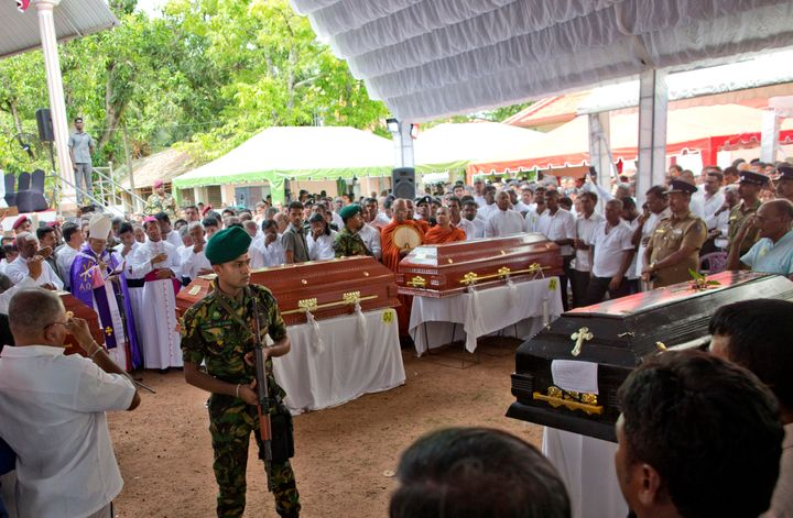 A soldier stands guard during a funeral service attended by Cardinal Malcolm Ranjith for Easter Sunday bomb blast victims at