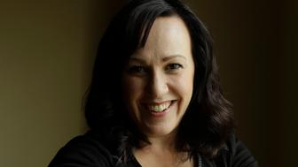 MJ Hegar pulls up her sleeve to reveal part of a tattoo that winds around her arm and back, for a portrait at her home in Round Rock, Texas,, on Thursday, Aug. 9, 2018. Nine years after being shot down in Afghanistan, winning a lawsuit against the federal government, and writing a book, Hegar is now running for a Texas congressional seat. Women with military experience _ many of them combat veterans _ are among the record number of female candidates running for office this year.  (AP Photo/Eric Gay)