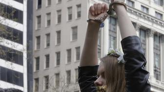 Headshot of a millennial generation protester wearing a flower garland holding her handcuffed arms aloft during a March On Tax Day to demand that United States President Donald Trump release his tax returns, at Bryant Park, Manhattan, New York City, New York, April 15, 2017. (Photo via EuropaNewswire/Gado/Getty Images)