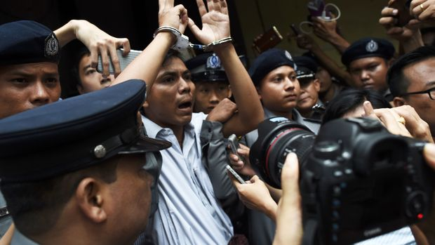TOPSHOT - Myanmar journalist Kyaw Soe Oo (C) is escorted by police after being sentenced by a court to jail in Yangon on September 3, 2018. - Two Reuters journalists were jailed on September 3 for seven years for breaching Myanmar's official secrets act during their reporting of the Rohingya crisis, a judge said, a case that has drawn outrage as an attack on media freedom. (Photo by Ye Aung THU / AFP)        (Photo credit should read YE AUNG THU/AFP/Getty Images)