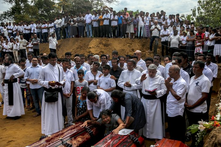 A woman weeps next to coffins during a funeral near St. Sebastian's Church in Negombo, Sri Lanka, April 23, 2019.