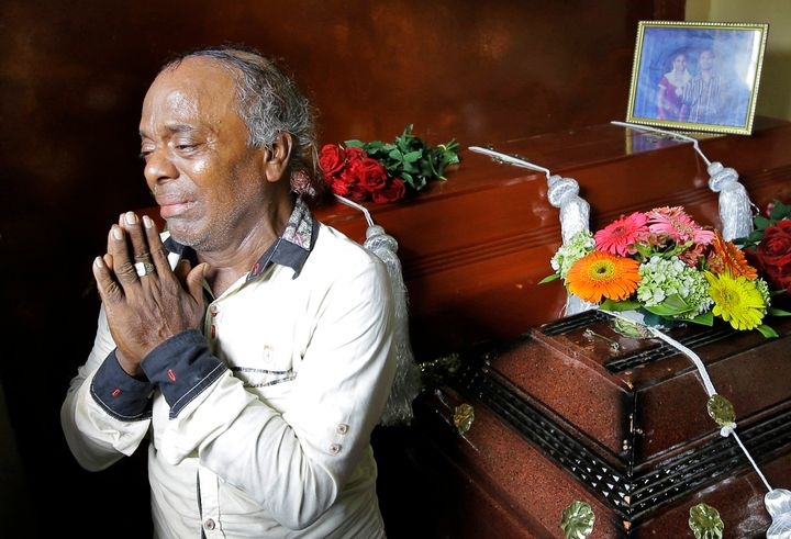 Baby Joseph Gomes prays next to the coffins of his family members who were killed in the Easter Sunday bombings in Colombo, S