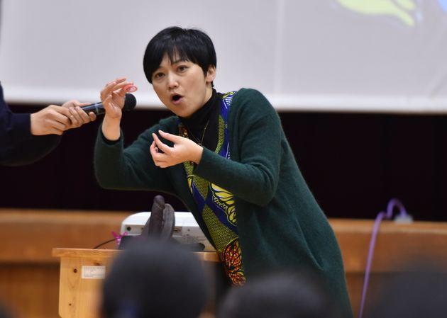 大津商業高校の1年生らにコンドームの付け方を教える清水美春さん=大津市