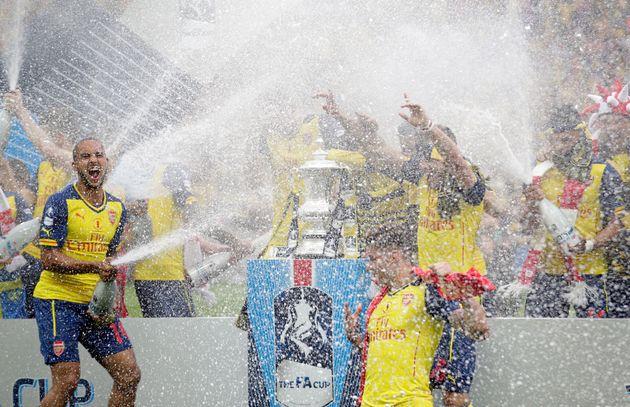 Theo Walcott (Arsenal), à gauche, pulvérise du champagne alors qu'il célèbre...